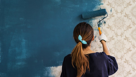 Women-painter-painting-the-walls-over-wallpaper-min